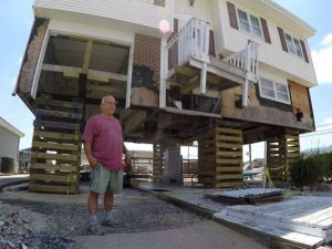 man in front of home destroyed by flooding