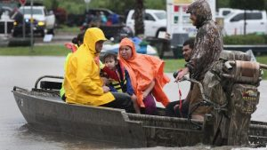 family being rescued by boat during flood
