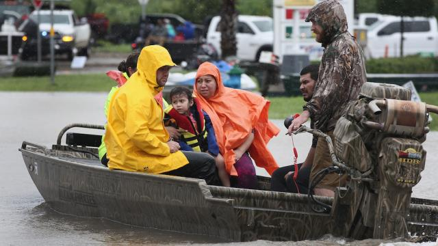 Man in small boat rescuing family from flooded area