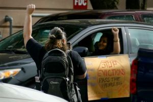 "two women with a fist in the air - one on foot one in a car, a sign on the car says ""STOP EVICTIONS"""